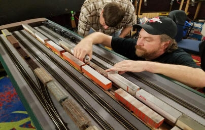 Brian sets up his train in staging as Kip packs up his train.